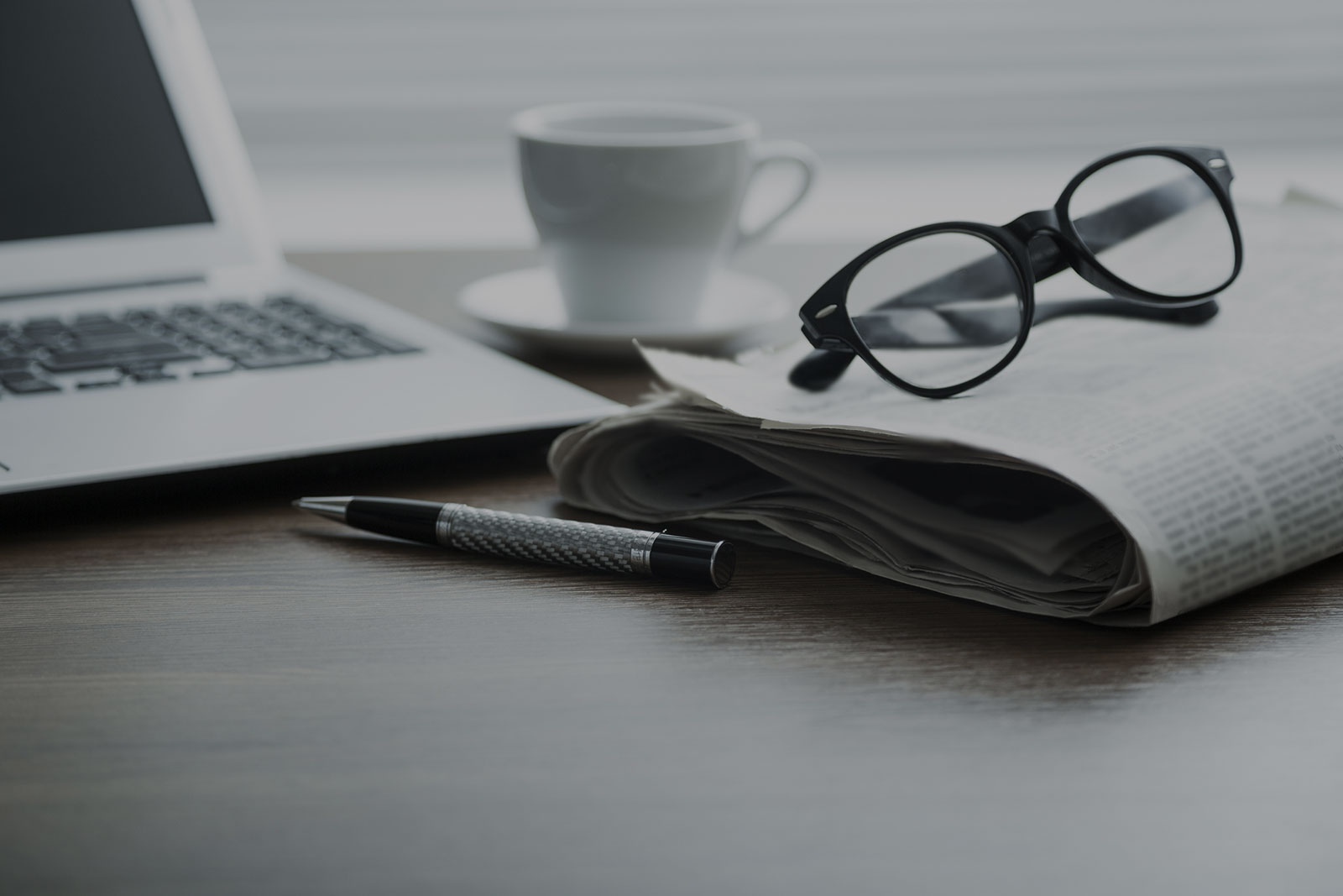 News & Publications Header Background - Desk with Laptop, Coffee, Glasses and Newspaper