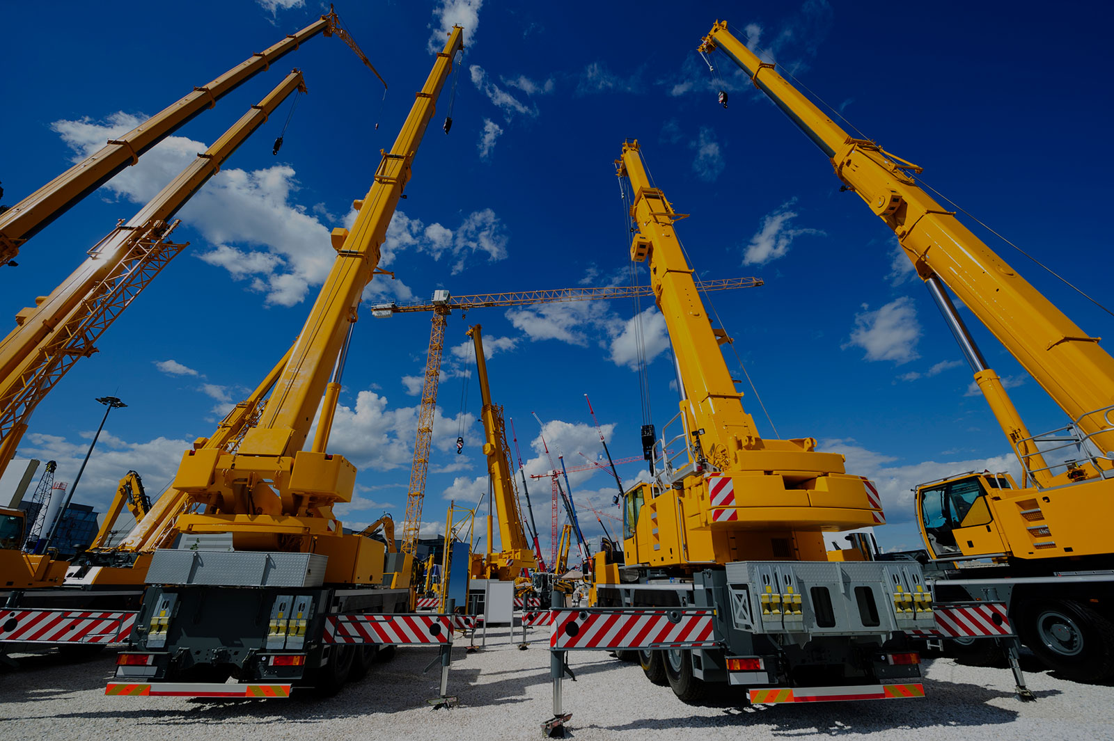 Equipment Leasing & Finance Header Background - Yellow Cranes Underneath Blue Sky